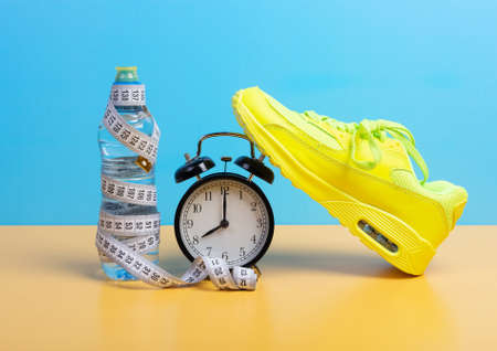 Weight loss and training concept with measuring tape, a bottle of water, and a sneaker on blue wall