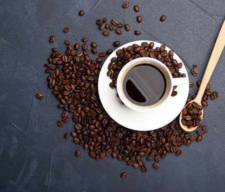 Coffee beans and cup of coffee on blue concrete background. Coffee in a white cup.