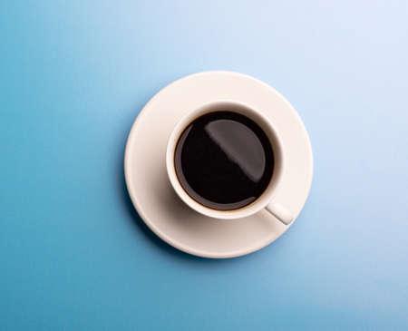 A cup of hot coffee on blue background. White cup of coffee in the morning.