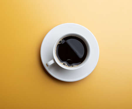A cup of hot coffee on yellow background. White cup of coffee in the morning. 版權商用圖片