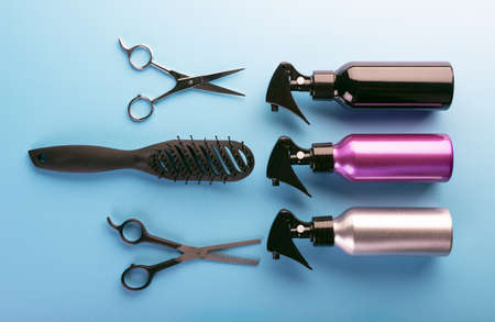 Hairdresser set with different tools on blue background. Professional equipment for haircut isolated, top view. Hair combs, scissors and sprayers.