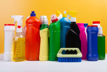Various cleaning supplies, detergents and cleaning products on yellow background