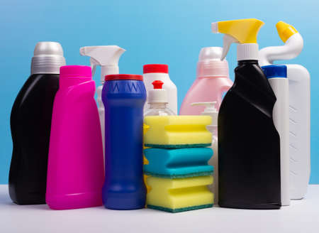 Various cleaning supplies, detergents and cleaning products on blue background.