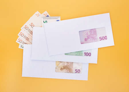 Stack of closed white envelopes with euro bills inside and banknotes beside over yellow background. Concept of income, bonuses or bribes. Corruption in business, illegal black salary