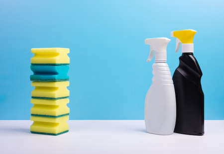 Window cleaner in a colorful plastic spray bottles and sponges on blue background. Cleaning concept. Standard-Bild
