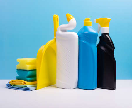 Various cleaning supplies, detergents and cleaning products on blue background