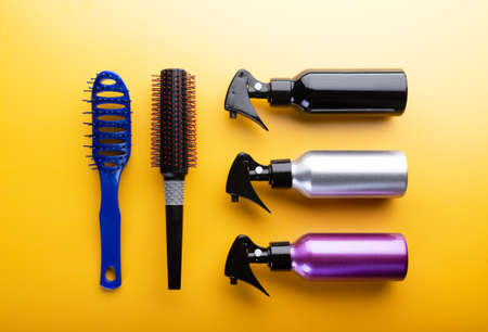 Hairdresser set with different tools on yellow background. Professional equipment for haircut, top view. Hair combs and sprayers. Standard-Bild