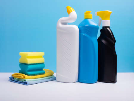 Cleaning concept with various plastic bottles canisters and sponges on blue background. Various detergents and the necessary attributes for cleaning.