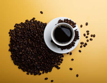 Coffee beans and cup of coffee on yellow background. Coffee in a white cup.