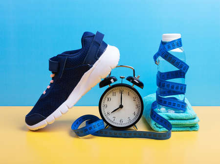 Running, weight loss concept with sneakers, bottle of water, towel, timer and measuring tape set over blue wall background