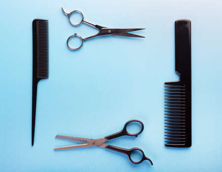 Professional tools for hairdresser on blue background: hair combs and haircutting scissors. Hairdresser equipment for hairstyle in salon or barbershop concept