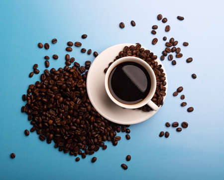 Coffee beans and cup of coffee on blue background. Coffee in a white cup.