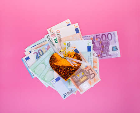 Business success, salary bonuses, profit, investment win and financial increase concept with gift box over euro bills pile on pink background.