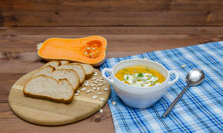 Pumpkin cream soup with pumpkin seeds. Healthy, vegetarian food. Bowl with soup and orange pumpkins on wooden table