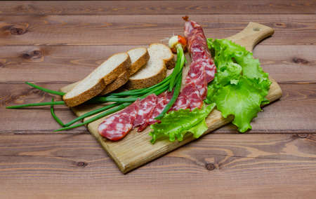 Chopped pork sausage, salad, onion and bread on wooden table Stock Photo