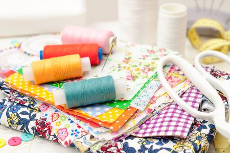 Couture, couture sur la machine à coudre, fournitures de couture, fils à coudre colorés, pièces colorées de tissu, aiguilles, centimètre, ciseaux de tailleurs sur fond en bois blanc Banque d'images - 68995466