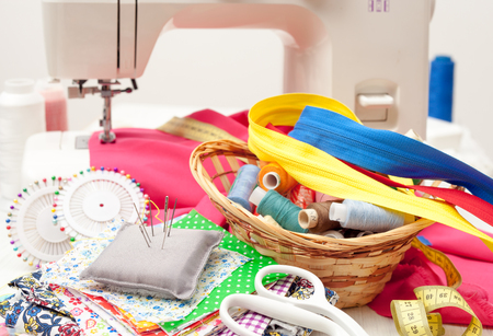 sewing, sewing on the sewing machine, sewing supplies, colored sewing threads, colored pieces of cloth, needles, centimeter, tailors scissors on white wooden background Reklamní fotografie - 68995475