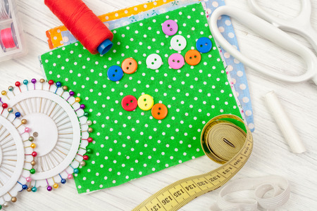 sewing, sewing on the sewing machine, sewing supplies, colored sewing threads, colored pieces of cloth, needles, centimeter, tailors scissors on white wooden background