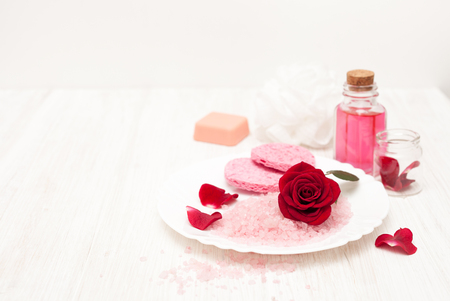 beauty of rose petals with their hands on white wooden background