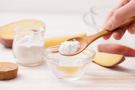 zeezout, zetmeel in de pot, snij de aardappelen in plakjes voor recepten van cosmetica thuis op een witte houten achtergrond