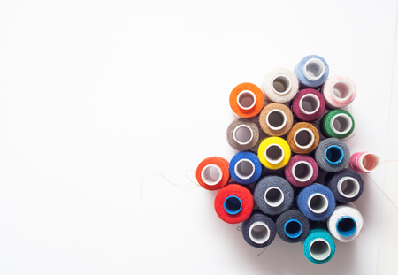 Colored thread coils on white background, sewing, place for text Stock Photo