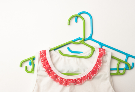 Childrens clothes on a hanger on a white background, place for text