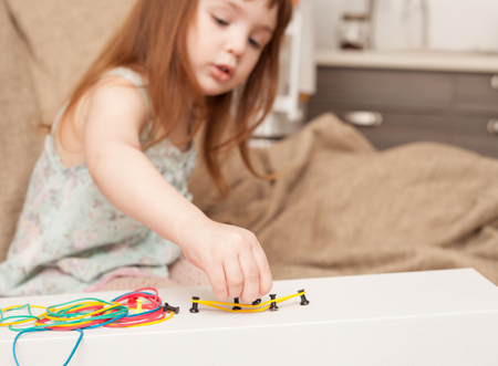The girl plays with multi-colored elastic bands and buttons. Games from hand-made materials with their own hands. Stock Photo