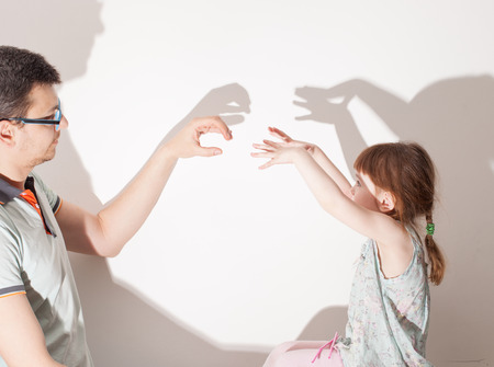 child plays with a parent in the theatre of shadows on a white wall