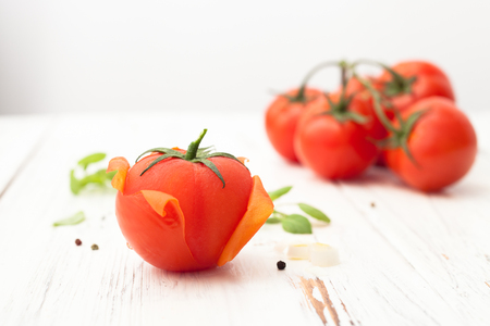 Tomato with purified skin and a bunch of tomatoes on white background. Background image.