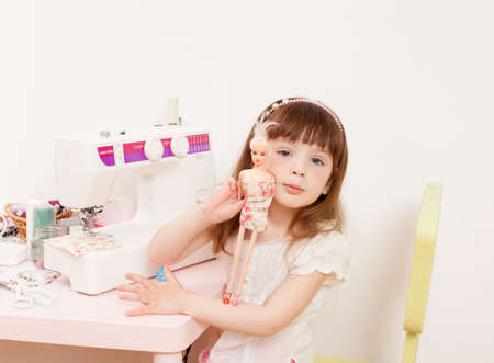 The girl tries on a piece of cloth on the doll. Next to the table with sewing accessories and sewing machine.