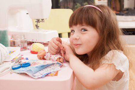Girl sitting on a chair next to the table and sewing machine. Plays fashion, dressing dolls in pieces of cloth. Stock Photo