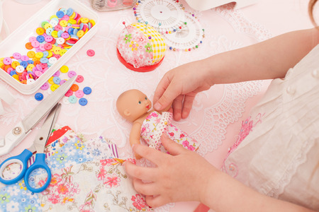 Girl playing fashion designer dressing the dolls in pieces of cloth. Next sewing machine, thread, buttons, needles, rubber and miscellaneous pieces of fabric. Stock Photo