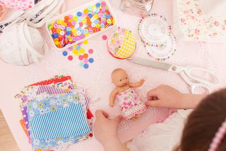 Meisje die manierontwerper spelen die de poppen in stukken van doek kleden. Volgende naaimachine, draad, knopen, naalden, rubber en diverse stukken stof.