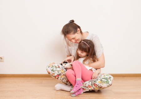 Woman sitting on the floor with his daughter and stroked the kitten. Mother and daughter smiling, enjoying the conversation. Place for text, background image.