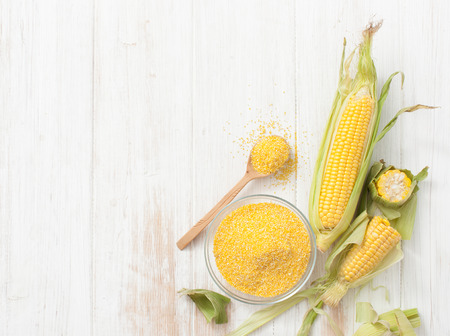 Corn grits for cereal and cobs of raw corn on a white table. Place for text. Archivio Fotografico