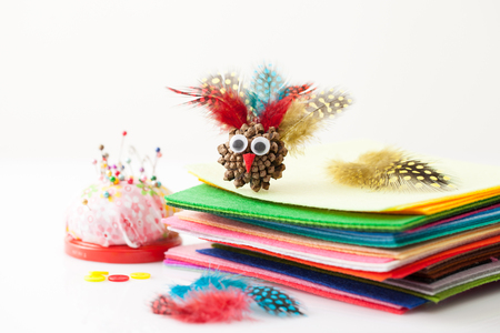 Crafts with the child for thanksgiving with natural materials: fir cone, feathers, felt. Place for text. Stock Photo