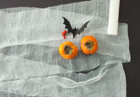 Background for Halloween from bandage and simulate paper pumpkins with a bat. An empty space to insert text. Stock Photo