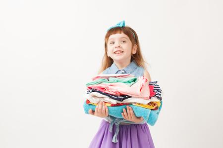 Meisjesholding gevouwen kleren in zijn handen op witte achtergrond. Een lege ruimte om tekst in te voegen.