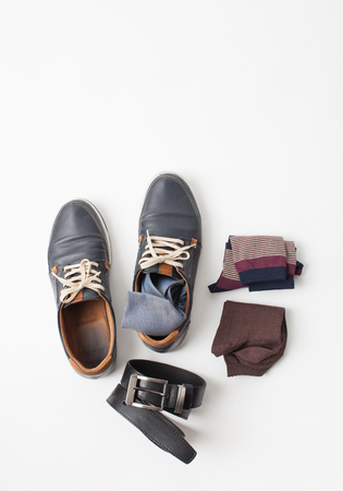 Set of mens blue shoes, belt, tie, socks on a white background. An empty space to insert text.