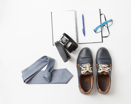 Set of mens blue shoes, tie, belt, glasses, Notepad with pen on white background.