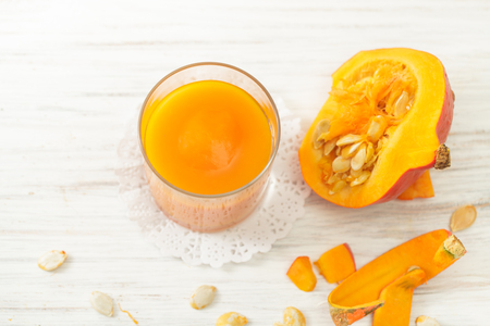 Cut the white pumpkin on the kitchen table. Recipes for pumpkin juice for diets. Place for text. Stock Photo
