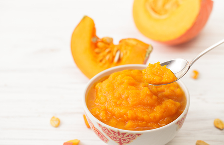 Cut the white pumpkin on the kitchen table. Recipes for pumpkin puree diets. Place for text. Stock fotó