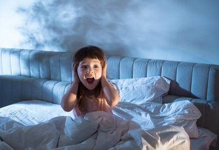 Nocne lęki dziecka. Bać się ciemności. Dziecko na łóżku w nocy. Puste miejsce na wstawienie tekstu.