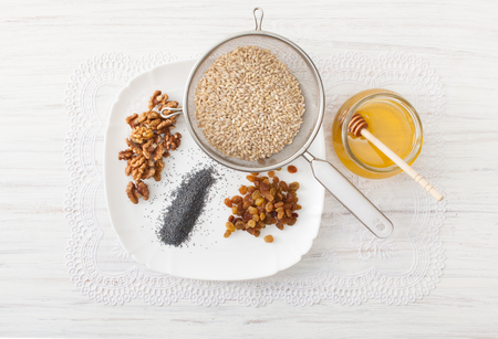 Recipes for Christmas dishes. Ingredients on a white table to corner wheat, nuts, raisins, poppy seeds, honey. Stock Photo