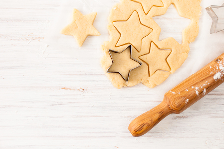The preparation of the biscuits. The dough for making Christmas cookies. The background image of the process of cookie making.