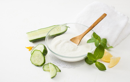 Homemade cosmetics with cucumber and sour cream on a white background. Detoxification skin vegetable masks. Stock Photo