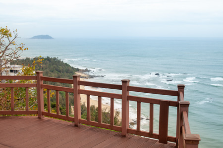 Wooden staircase along the sea coast with a viewing platform among the boulders and tropical greenery