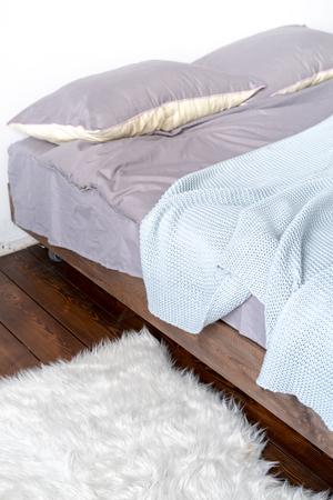 Unmade bed with grey linen and fur rug Foto de archivo