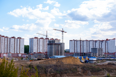 Construction of a multi-storey building with cranes in the area of new buildings near the river 免版税图像