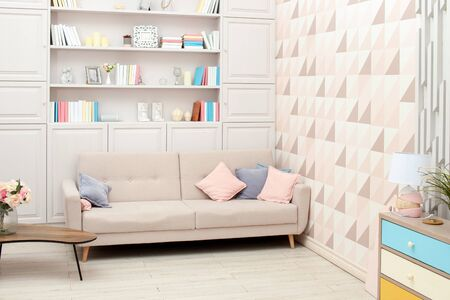 Pastel-colored interior with beige sofa and built-in bookcase